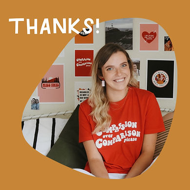 "A photograph of Jenny sitting in bed smiling at the camera. She is wearing a red tshirt with white retro text that reads ""compassion over comparison please""."