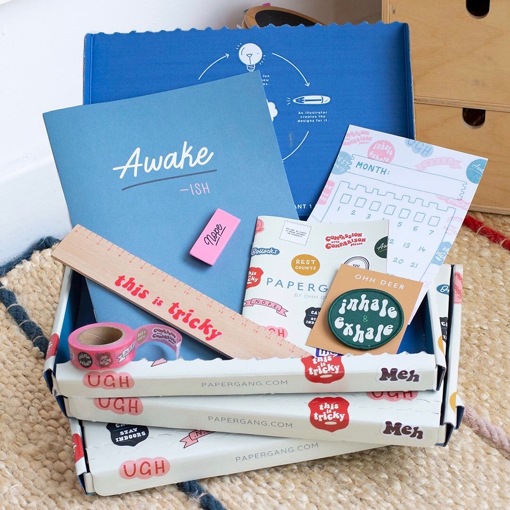 A photograph of an open cardboard box in a mix of stationery items inside. It includes a blue notebook, a wooden ruler, a pink eraser, pink washi tape, a green embroidered patch and an information booklet.