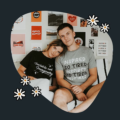 "A photograph of Jenny and her boyfriend Ryan sitting in bed. Jenny has her head resting on Ryans shoulder. Jennys tshirt is navy and features cream text that reads ""invisible not imaginary"". Ryans tshirt is grey and features black and white text that repeats ""inspired, so tired""."