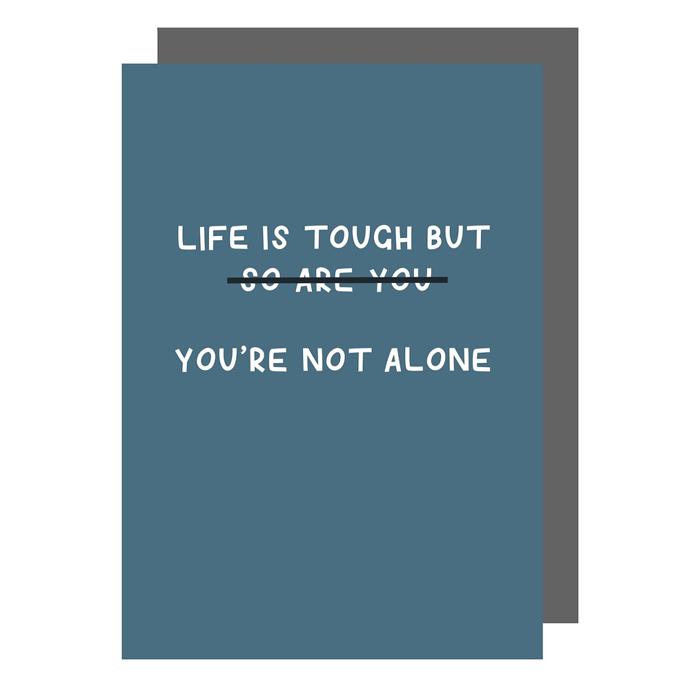 """A flat illustration of a mid tone blue greeting card laying over a grey envelope. The card features white handwritten text in block capitals. The text changes the phrase """"life is tough but so are you"""" to """"life is tough but you're not alone""""."""