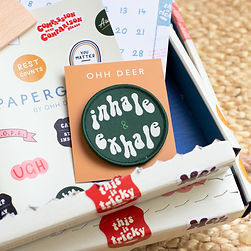 """A photograph of a dark green circular patch. The patch features white handwritten text that reads """"inhale and exhale"""". The patch is attached to a peach backing card. Photograph credit goes to Ohh Deer."""