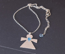 Sterling silver angel pendant with sky blue topaz heart