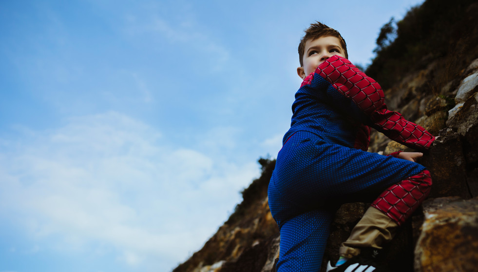 Boy with a spiderman costume climbing a mountain