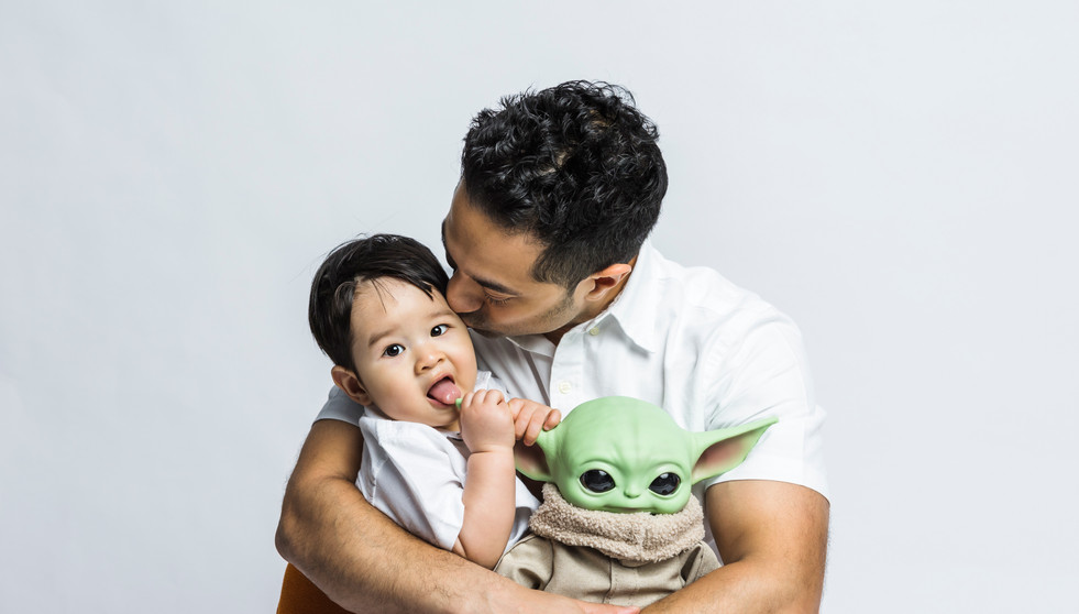 Father kissing his son on the cheek while he is sucking his favorite teddy bear