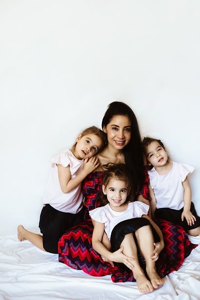 Studio photo with white background of a mother and her triplets daugthers