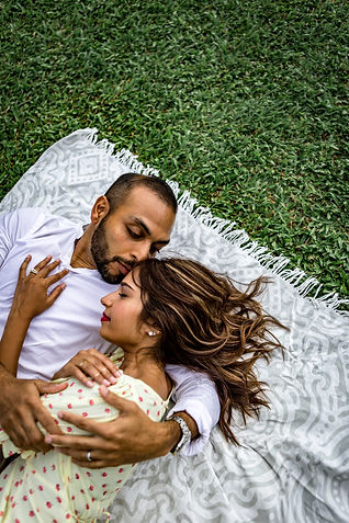 Man and woman liying on the grass while hugging