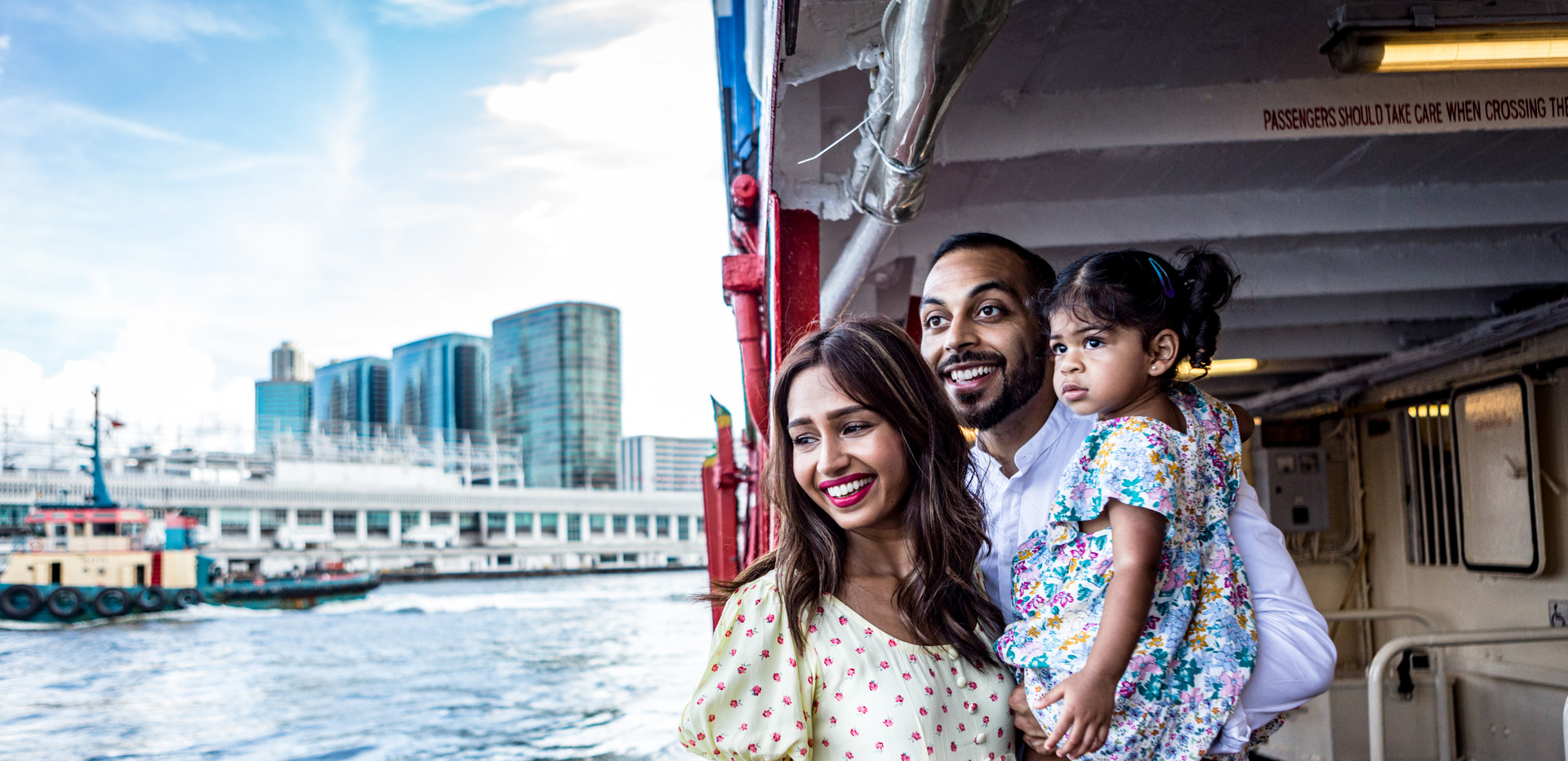 Family of three riding the Star Ferry while looking at the view
