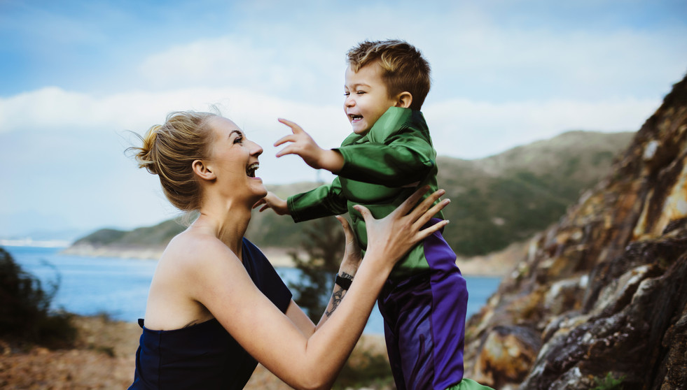 Mother catching his son while he jumps from a rock dressing a superhero costume
