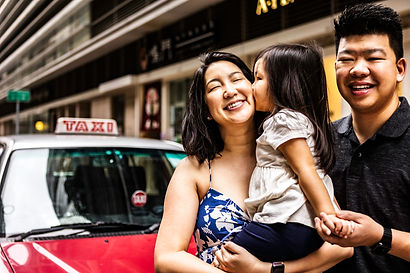 Family of three in front of a red Taxi in Sheung Kwan