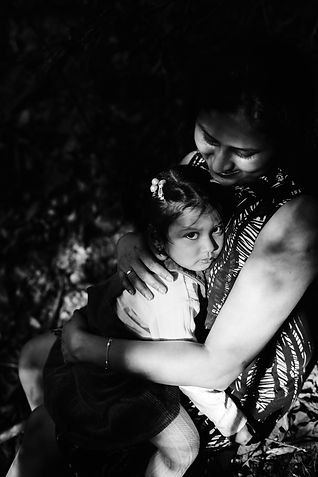 Mother hugging her daugther under the tree shades
