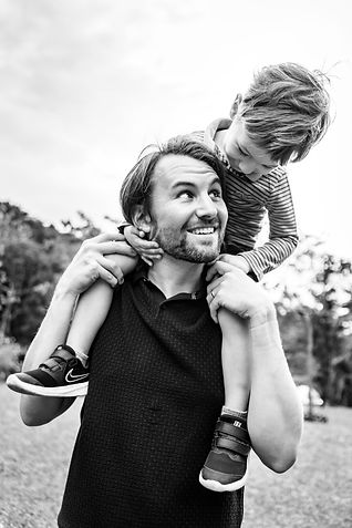 Boy being carry in his father shoulder looking each other