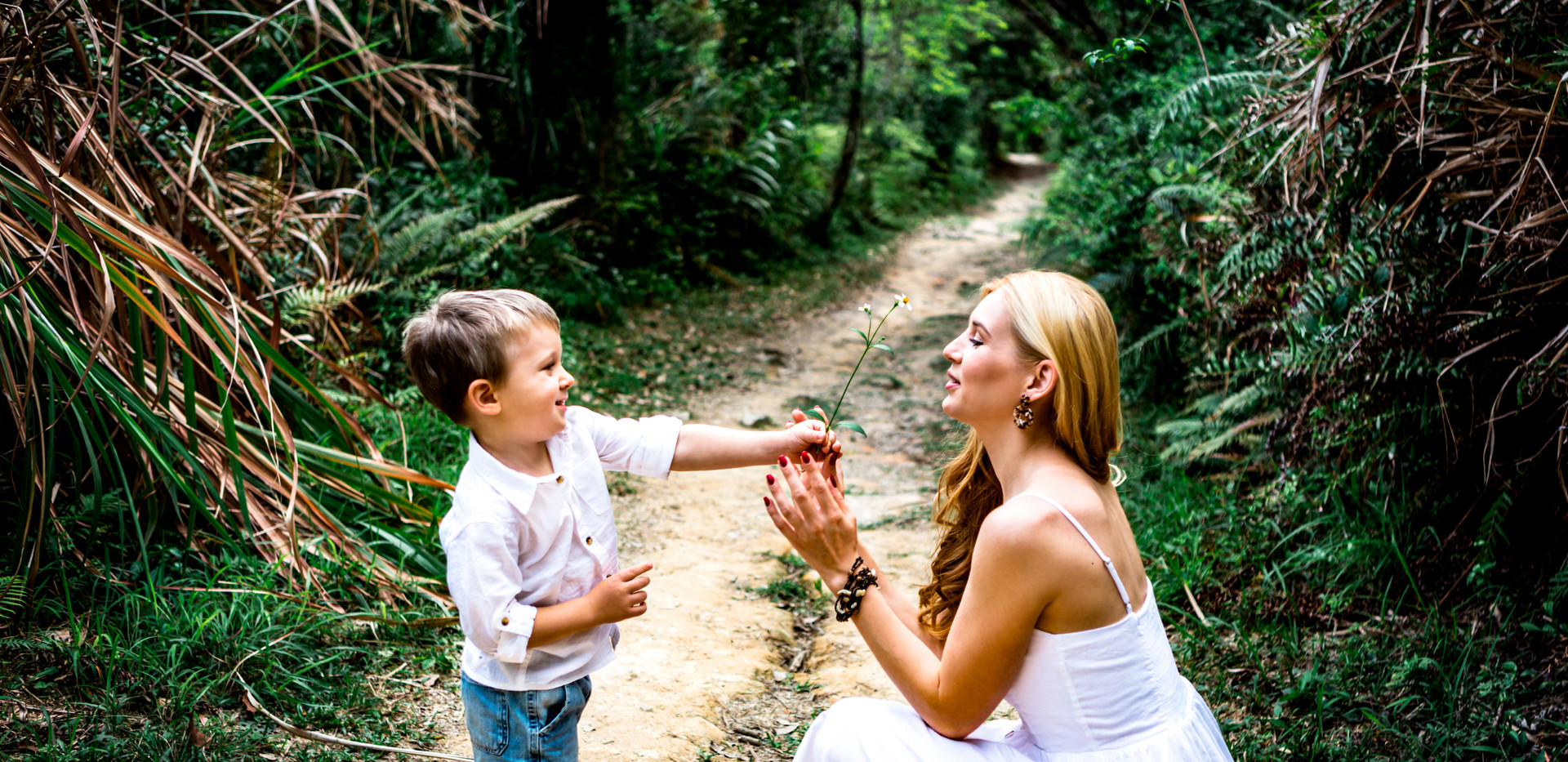 Boy giving her mom a white flower