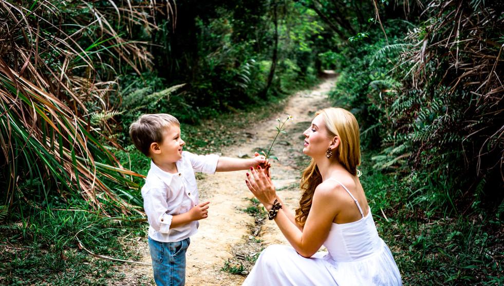 Boy giving her mom a white flower