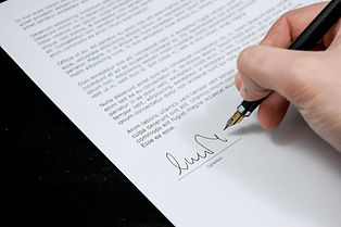 Hand signing a document with a fountain pen
