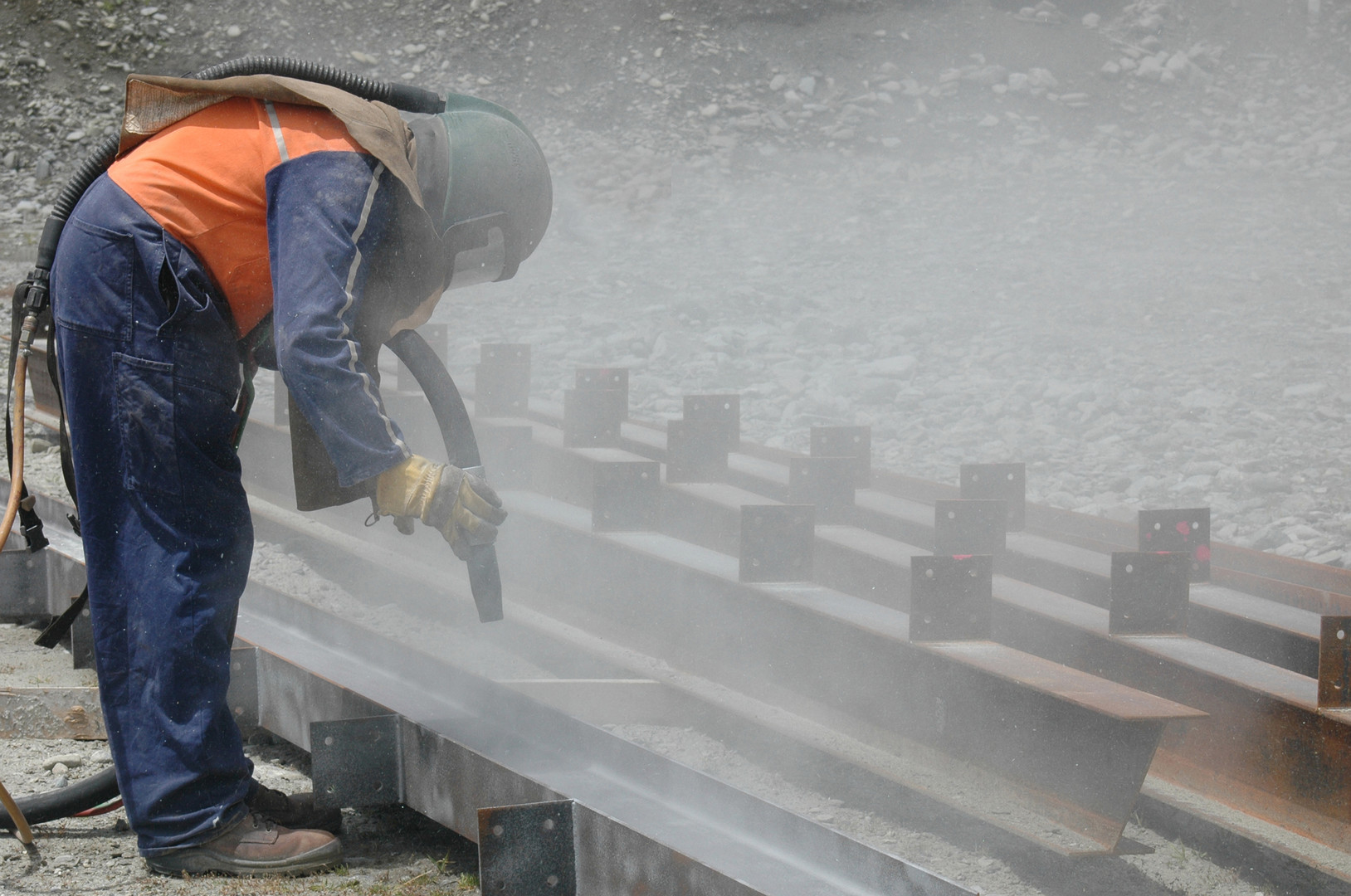 tradesman sandblasting I beams for build