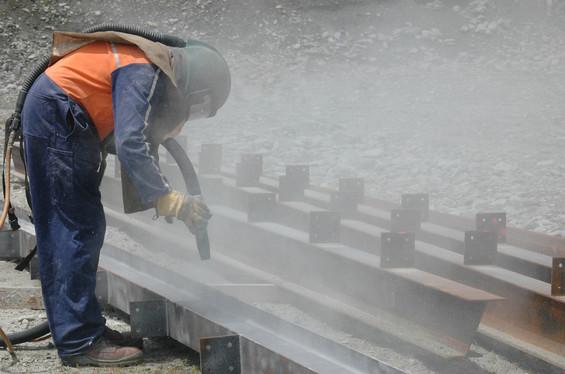 tradesman sandblasting I beams for build