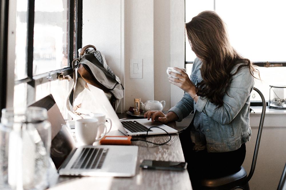 Frau vor Laptop mit Kaffee in der Hand
