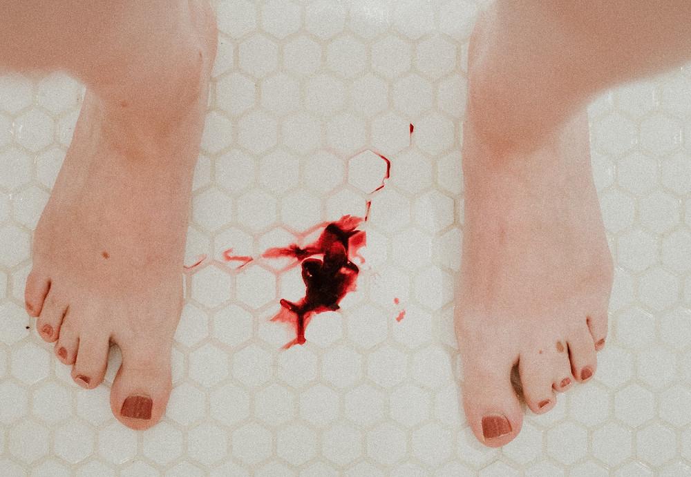 Frau steht in Dusche, bekommt Periode, Blut, ihre Tage