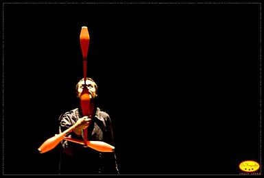 Circus, contemporary circus, Chicago circus, workshops, masterclasses, workshop, masterclass. Guillermo Leon de Keijzer. One juggler performing in a black theater space where he is balancing one orange club atop another orange juggling club and holding two more clubs trapped in a pattern.