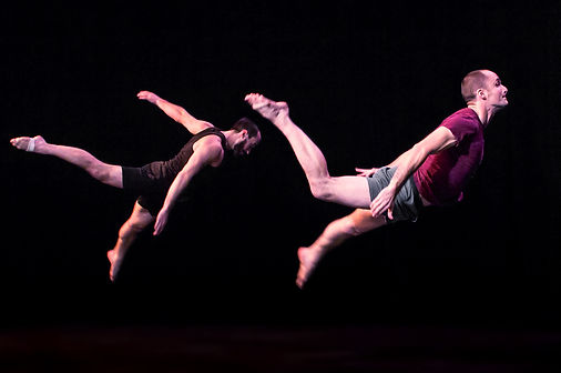 Two acrobats flying through the air. One is wearing a red shirt, the other is wearing a black shirt.  They are in a totally darkened space. Circus, contemporary circus, Chicago circus