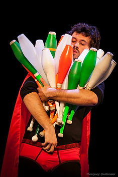 Circus, contemporary circus, Chicago circus, workshops, masterclasses, workshop, masterclass. Guillermo Leon de Keizjer. One juggler wearing a superhero costume and carrying an absurd amount of juggling clubs in his arms.
