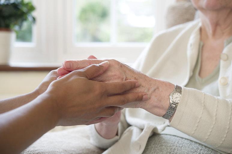 Elder woman and her caretaker, holding hands, seniors