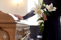 woman-with-lily-flowers-and-coffin-at-fu
