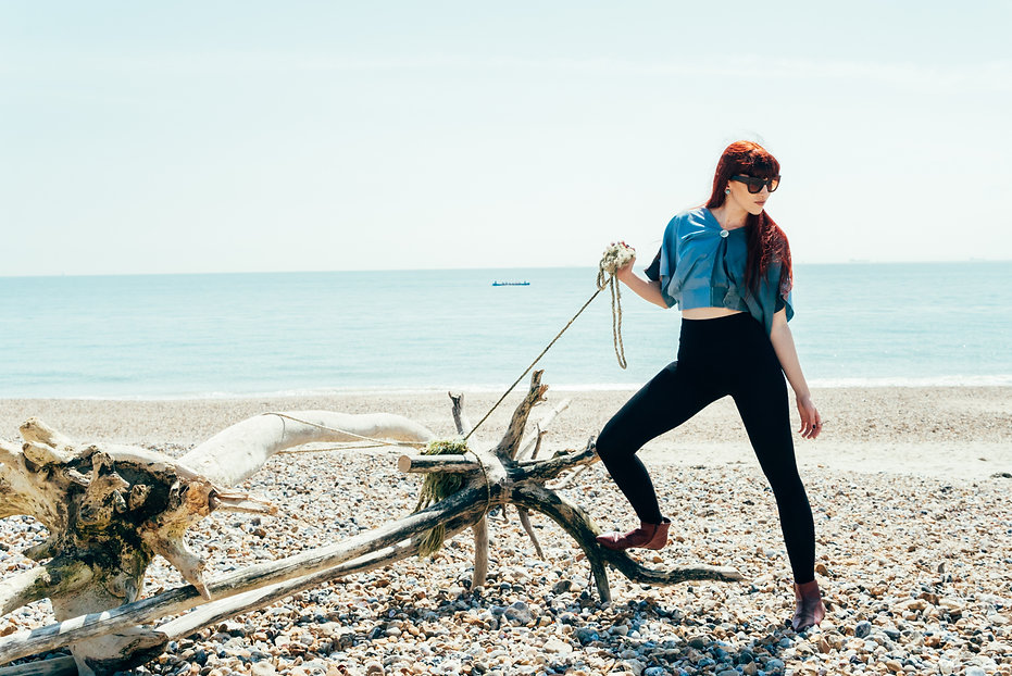 Model holding a rope tied to driftwood on beach; model wearing leggings and upcycled blue top.