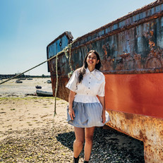 Model wearing white collar dress with striped extension skirt. Model is standing on a deserted beach, smiling next to a colourful boat with rust and maroon stripes