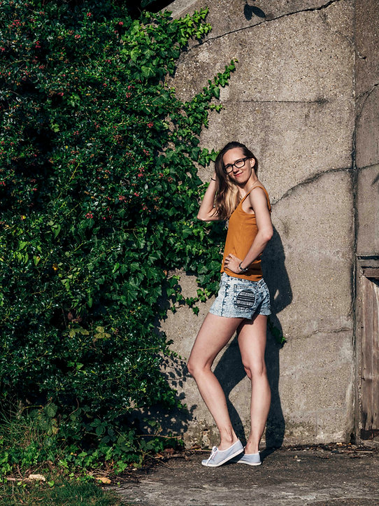 Model wearing light denim shorts with circle pocket on back and orange vest next to ivy wall.