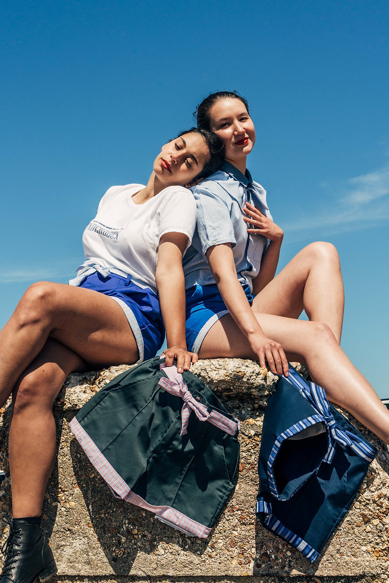Models sitting on a rock holding UNDERDOCK shorts - close up.jpg