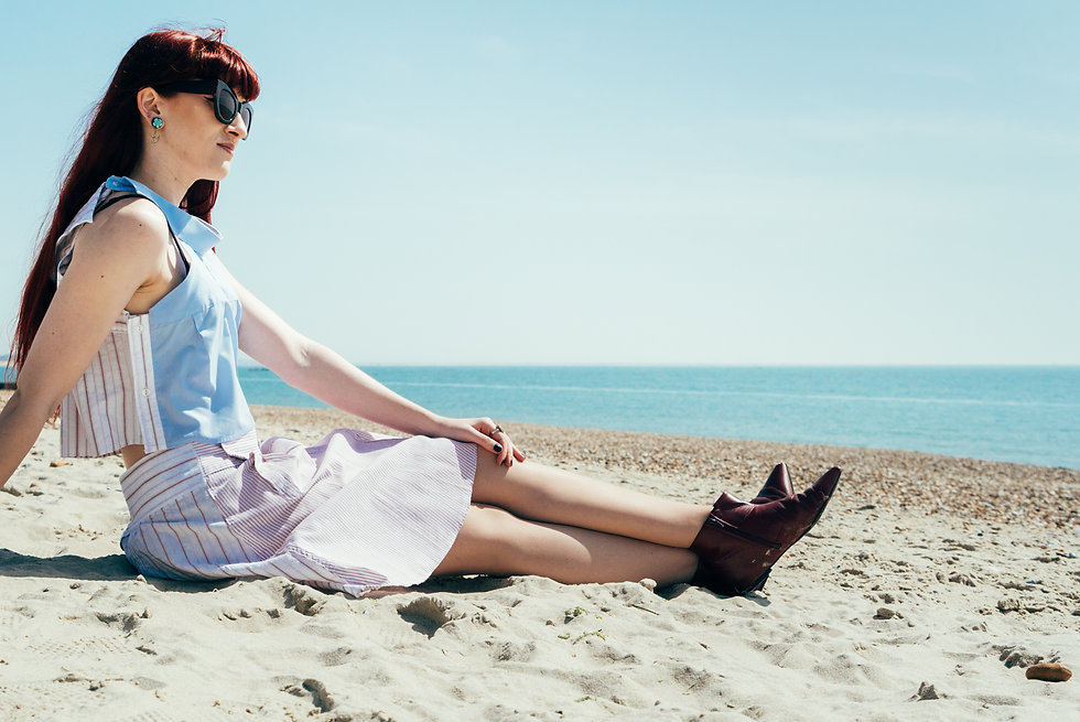 Model on beach, sitting, looking at the sea. Wearing upcycled pink and blue outfit.