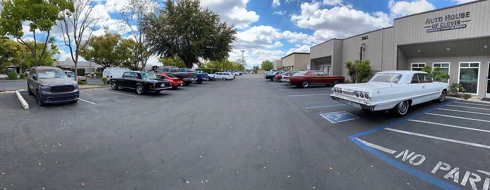 View of front parking lot with assorted vehicles at Auto House of Clovis