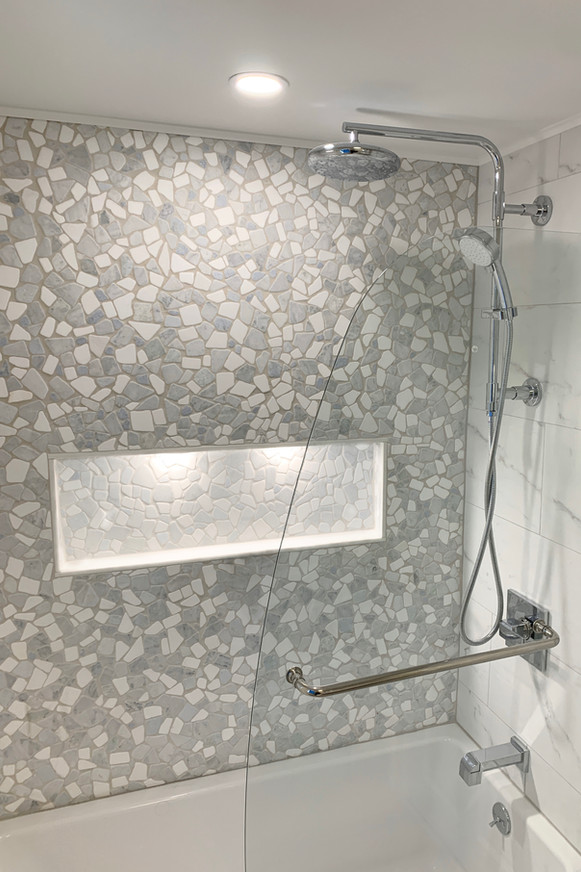 shower with mosaic tile feature wall, shelf, and hinged swing door