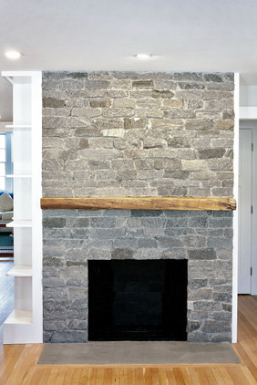 stacked stone fireplace with reclaimed wood mantel