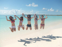 girls jumping on coco cay