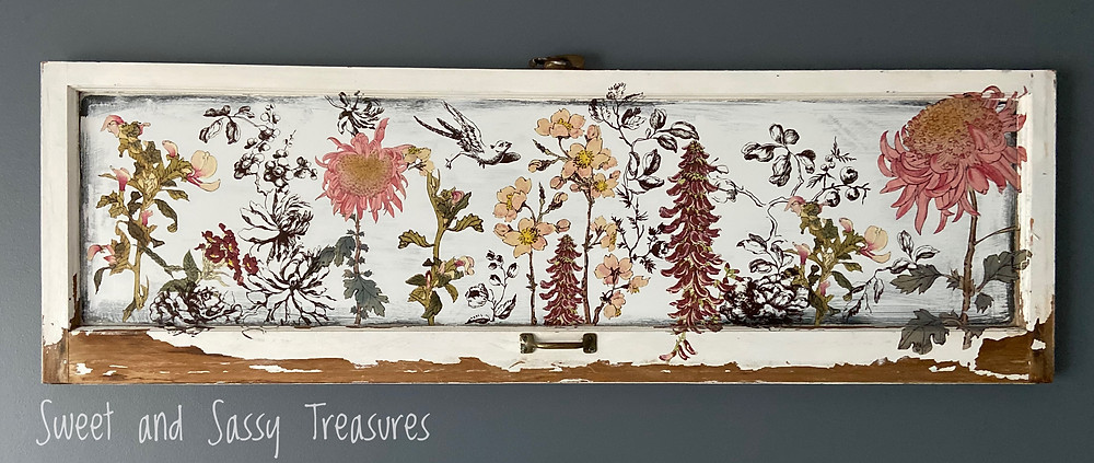 An old vintage window becomes wall art by using chalk based paint and a decorative, floral, rub on transfer