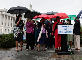 U.S. Representative Yvette D. Clarke and other members of Congress carry umbrellas as they arrive for the start of a news conference on the treatment of Haitian immigrants at the U.S. border in Texas, in Washington, D.C., U.S., September 22, 2021