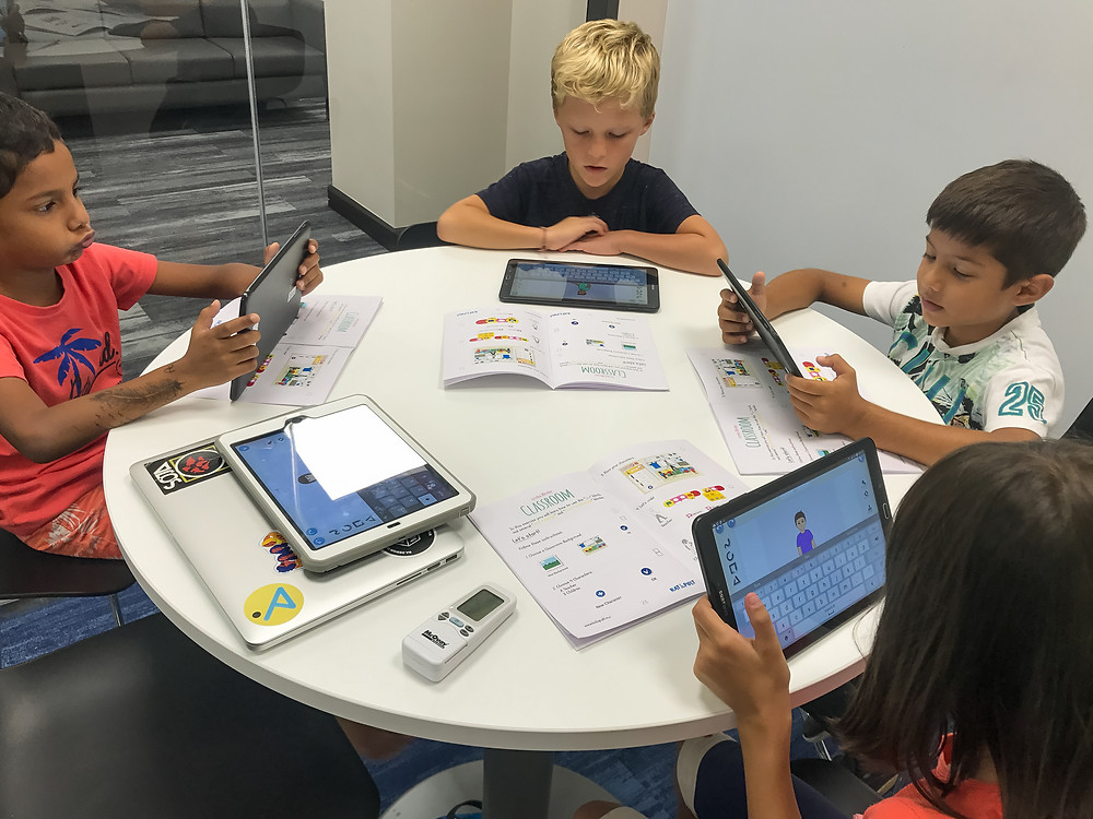 Kids learning how to code characters using tablets