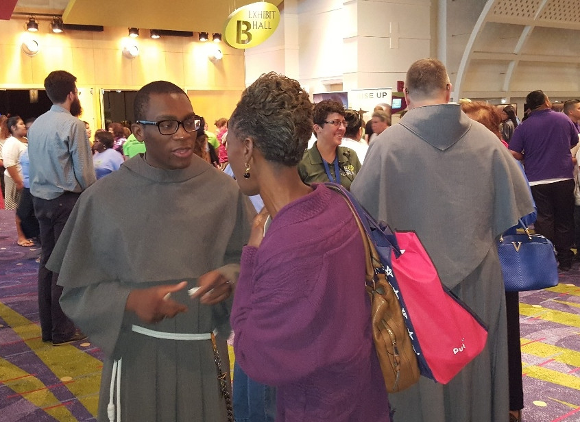 Friar Franck and Fr. John mingling and speaking with attendees