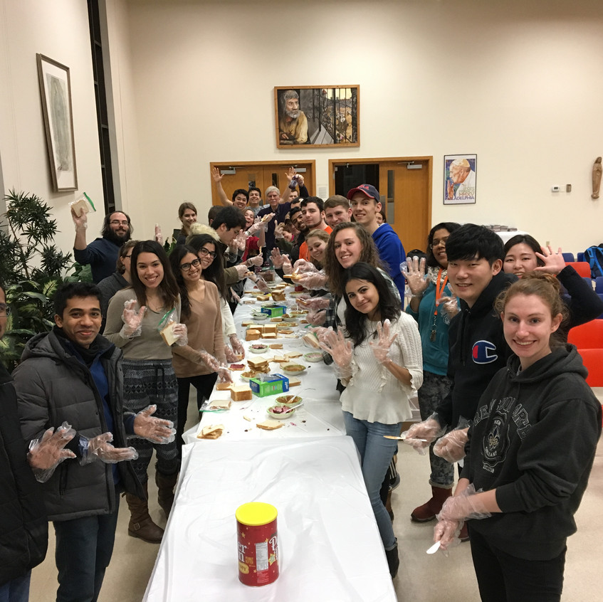Students gather to prepare sandwiches for the poor.