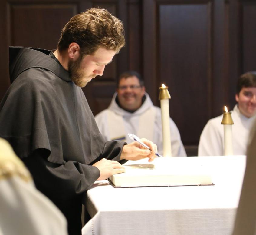 Friar Jason signs the Book of Profession joyfully observed by Fr. Matt Foley, OFM Conv. & Joseph Krondon