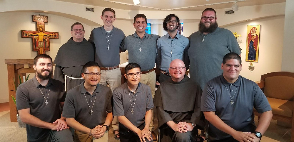Eight men and their formation directors. The San Damiano Cross in seen in the background.