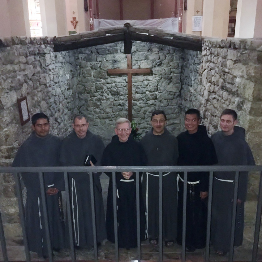 """The five (1 from OLA, 1 from St. Joseph Cupertino Province, and 3 from our Province Custody of Glessed Agnellus of Pisa) with Fr. James, who directed their final days of retreat at the Order's protoconvent Rivo Torto. Here they are standing in the """"Sacro Tugurio"""" (""""Sacred Hut"""") of Rivo Torto. Sorry about the glare in their eyes."""