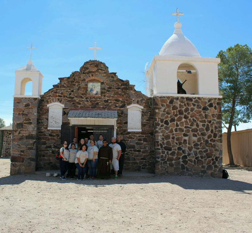 Students, Father Andy, and Friar Ponchi standing in front of the church.