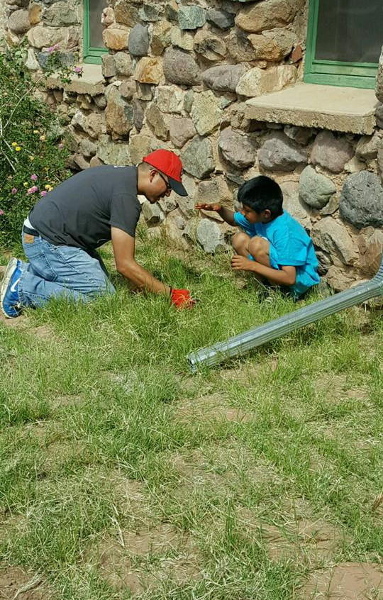 Student, Angel De La Rosa, pulling weeds and talking with a Native boy