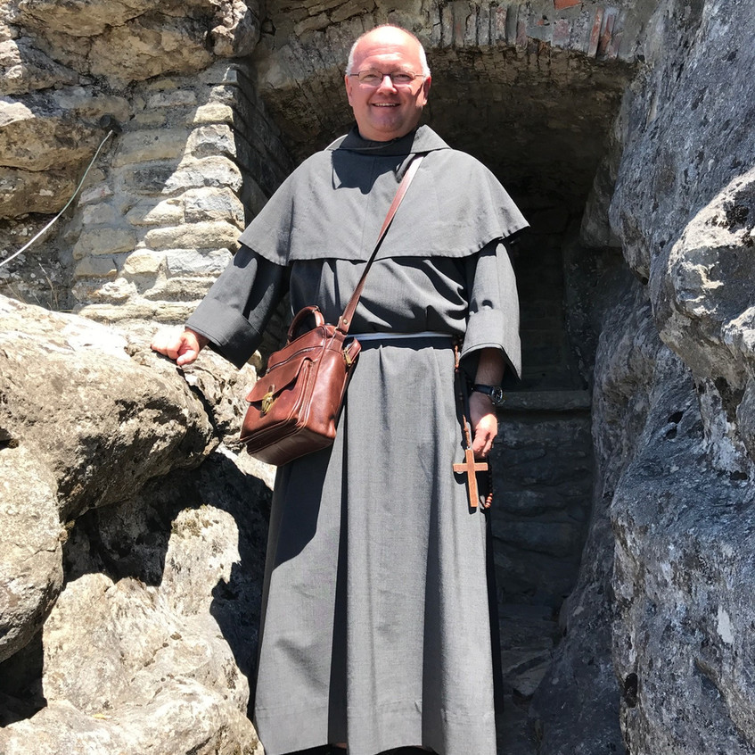 Friar Brad just outside the cave of Brother Leo, St. Francis' secretary and friend.