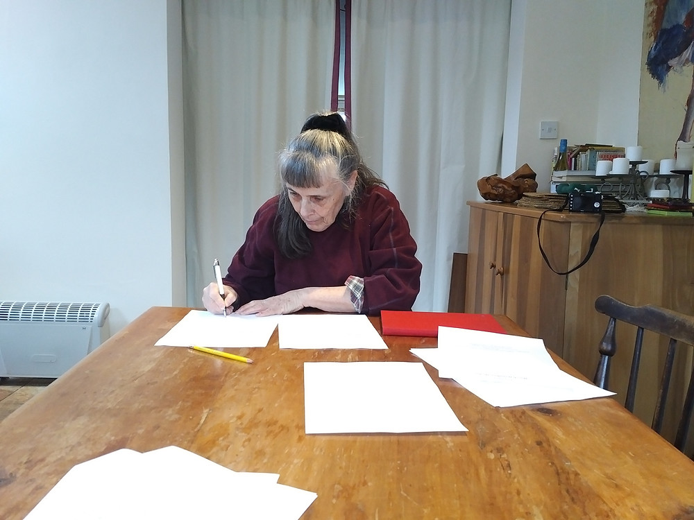 Author signing contract at a table.
