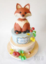 This baby shower cake features a scultped fox sitting atop a birch tree stump adorned with forest foliage