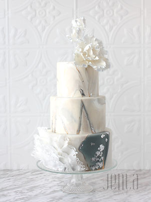 Bold high contrast marbling on this wedding cake is balanced by asymetrical ruffles and light, abstract sugar flowers - JENLA Cake, Toronto